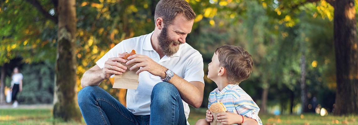 Far og sønn nyter et enkelt måltid i parken